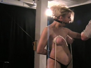 Exposed female stands yielding and endures harsh bdsm