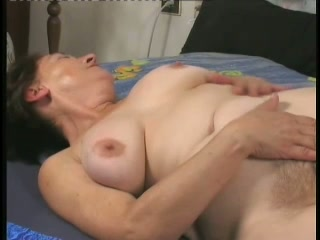 Busty and lascivious old whore on the bed pokes herself with a big toy