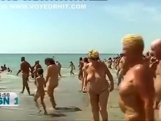 Mature Spanish nudists walk around the beach completely naked